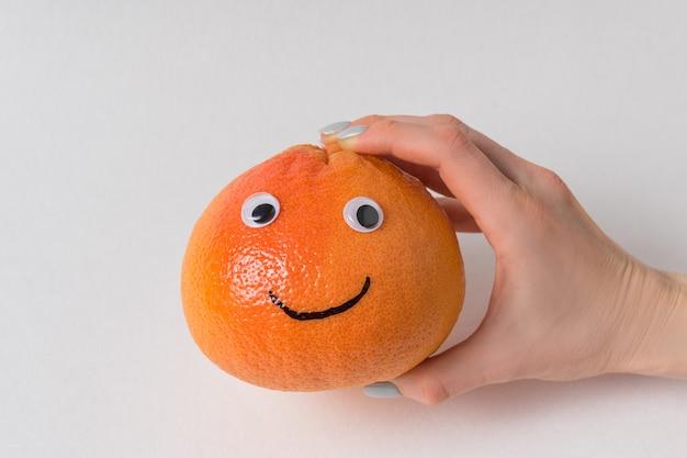 Main tenant un gros smiley orange sur fond blanc. pamplemousse aux yeux écarquillés et sourire