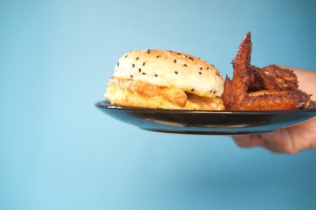 Main tenant un hamburger de boeuf sur fond bleu