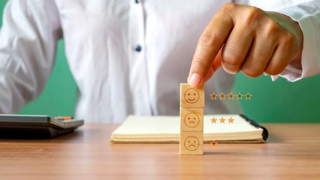 Main tenant l'icône happy sur un bloc de cube en bois sur un concept d'enquête de satisfaction annuelle d'entreprise de bureau