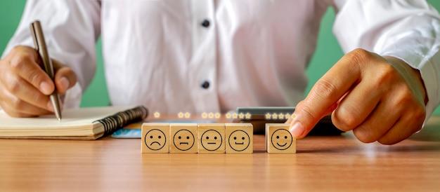 Main tenant une icône heureuse sur un bloc de cube en bois sur la table sondage annuel de satisfaction des entreprises