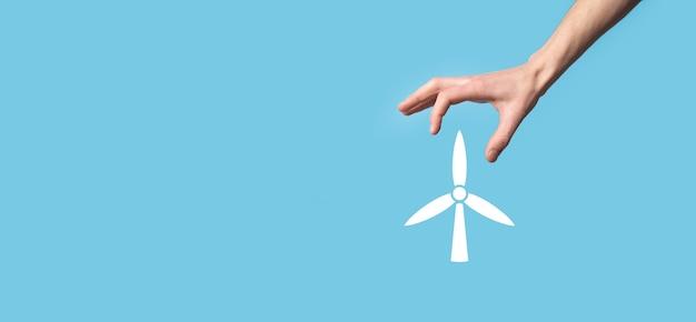 Main tenant une icône d'un moulin à vent qui produit de l'énergie environnementale sur fond bleu.