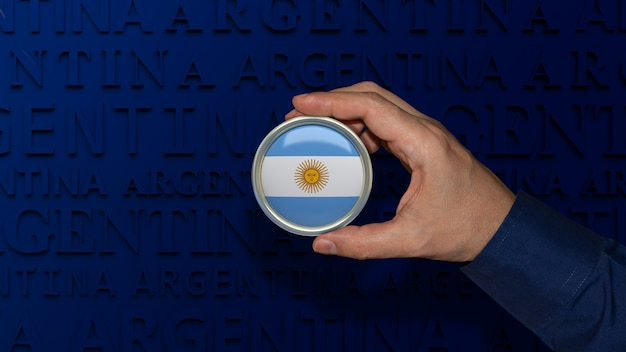 Une main tenant un insigne du drapeau national argentin sur fond bleu foncé