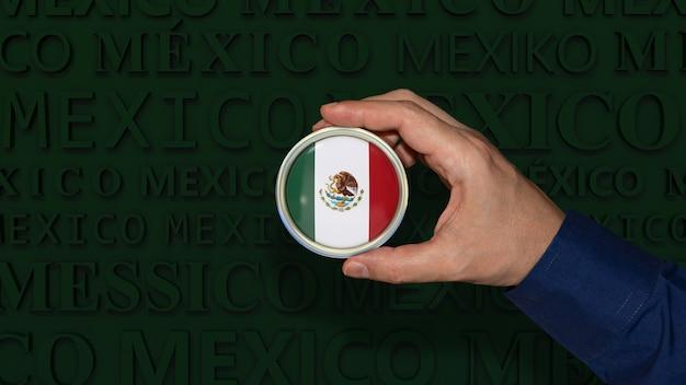 Une main tenant un insigne du drapeau national mexicain sur fond vert foncé