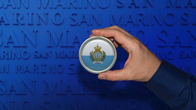 Une main tenant un insigne du drapeau national de saint-marin sur fond bleu