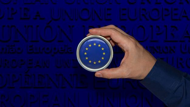 Une main tenant un insigne du drapeau de l'union européenne sur fond bleu foncé