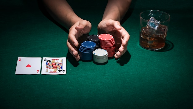 Main tenant des jetons de poker sur la table de poker