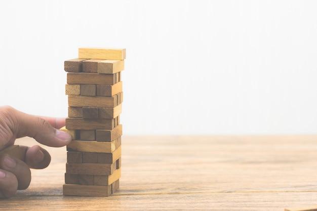 Main tenant un jeu de blocs de bois. risque d'investissement et incertitude dans le logement immobilier m