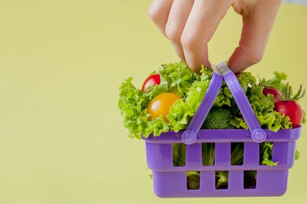 Main tenant des légumes frais dans le panier sur fond jaune