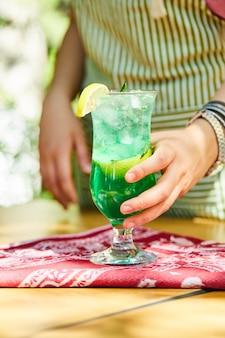Main tenant une limonade sur table en bois.