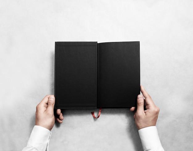 Main tenant un livre ouvert vierge avec demi-titre noir