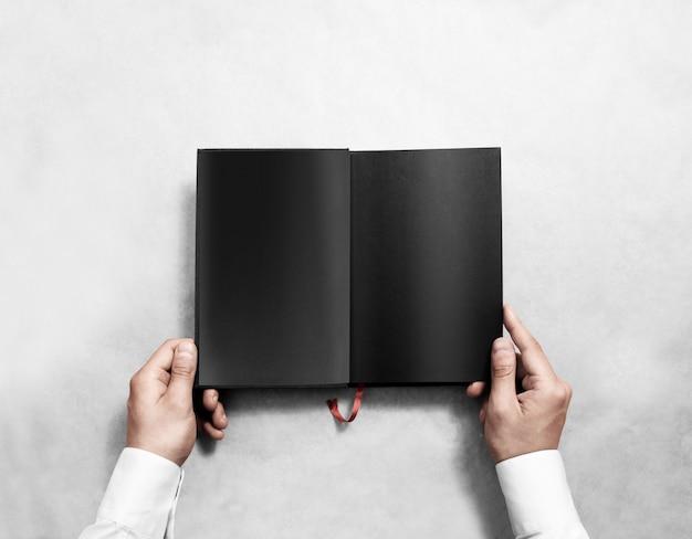 Main tenant un livre ouvert vierge avec des pages noires