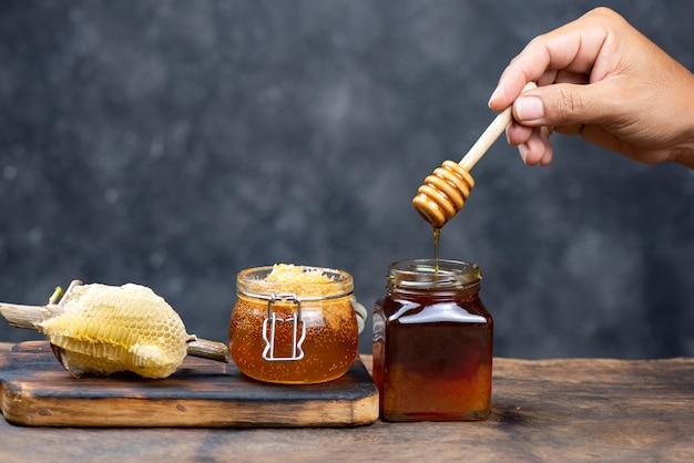 Main tenant une louche de miel en bois