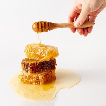 Main tenant la louche sur la tour en nid d'abeilles
