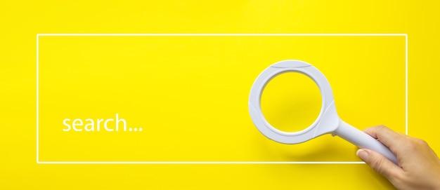 Main tenant la loupe sur fond blanc avec la recherche de texte. créativité de l'entreprise.
