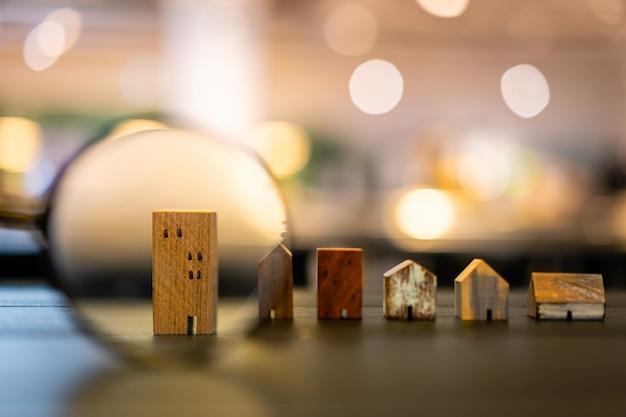 Main tenant une loupe et regardant le modèle de maison