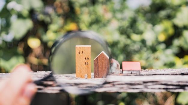 Main tenant la loupe et regardant le modèle de maison,
