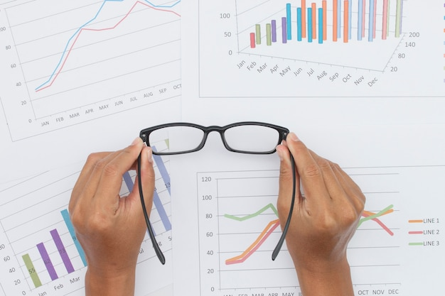 Main tenant des lunettes avec rapport sur le marché boursier