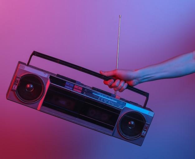 Main tenant un magnétophone radio rétro. en lumière dégradée néon bleu-rouge. culture pop. vague rétro des années 80