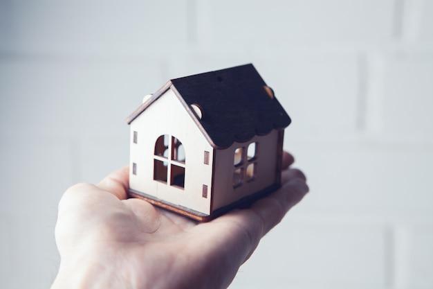 Main tenant une maison sur fond blanc