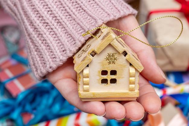 Main tenant la maison maison sapin de noël décoration fourrure épinette jouets de noël.