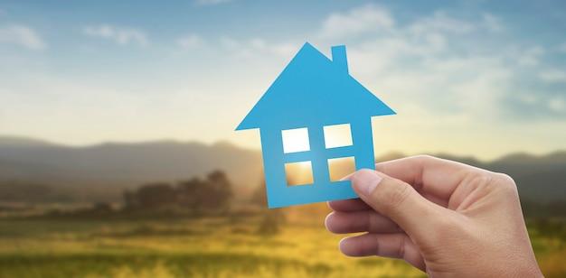 Main tenant la maison de papier bleu avec fond de paysage