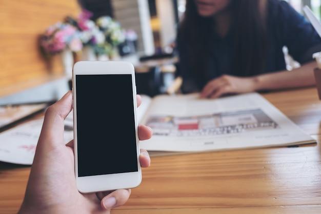 Main tenant maquette smartphone avec une femme lisant un livre au café