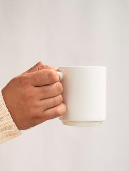 Main tenant une maquette de tasse