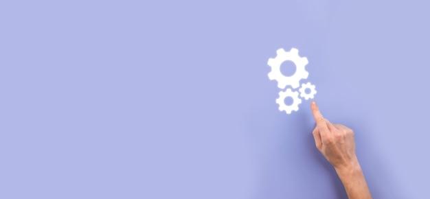 Main tenant un mécanisme d'engrenages métalliques et de roues dentées représentant le concept de travail d'équipe d'interaction, groupe de prise de main de roue d'engrenages à crémaillère virtuelle