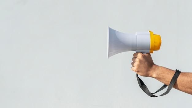 Main tenant un mégaphone pour protester