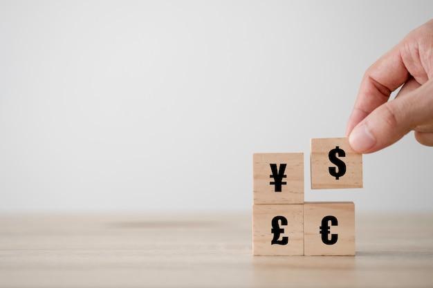 Main tenant et mettant le signe du dollar américain est imprimé sur un écran en bois cube en yuan yen euro une devise livre sterling. concept d'échange de devises et de forex.