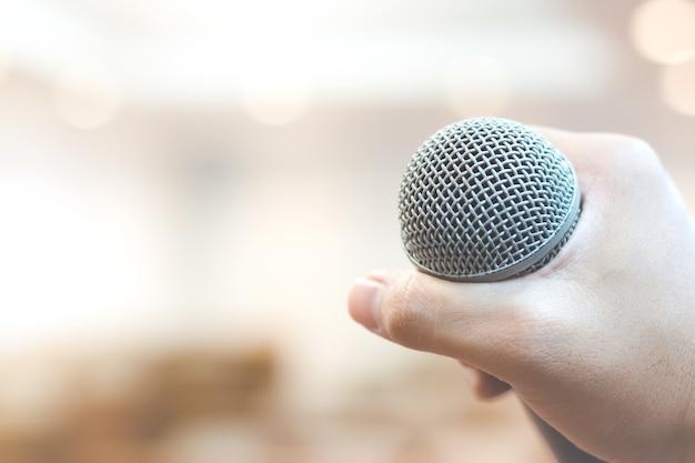 Main tenant le microphone sur l'arrière-plan flou