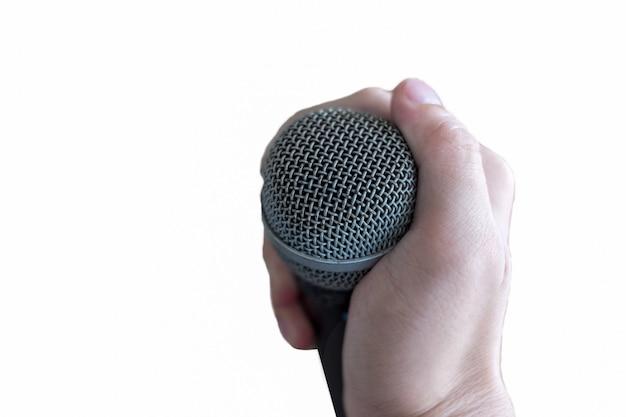Main tenant un microphone, isolé sur fond blanc