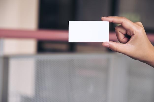 Une main tenant et montrant une carte de visite vide au bureau