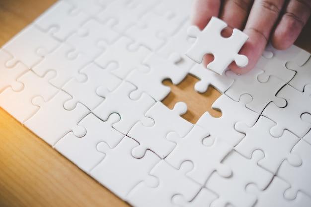 Main tenant le morceau de puzzle vide avec fond de cadre de papier.