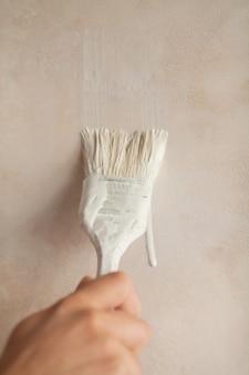 Main tenant le mur de peinture au pinceau. réparation