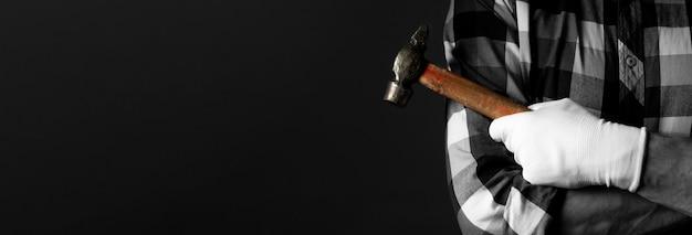 Main tenant l'outil marteau avec fond noir et place pour le texte. bannière publicitaire.