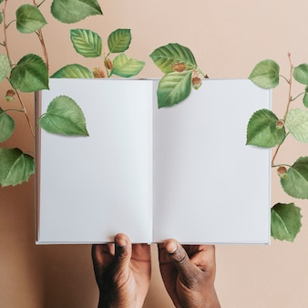 Main tenant une page de cahier vierge avec des feuilles vertes