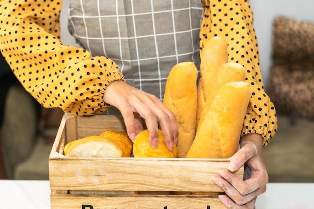 Main tenant le pain de seau frais dans la boulangerie