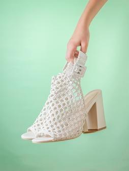 Main tenant une paire de chaussures en cuir d'été sur un mur vert. chaussures d'été en cuir pour femmes.