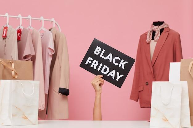 Main tenant une pancarte black friday avec des vêtements sur le cintre en arrière-plan