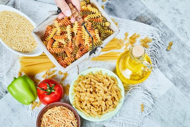Main tenant un panier de pâtes fusilli crues avec un assortiment de pâtes et de légumes sur la table en marbre.