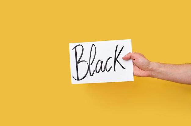 Main tenant un papier cartonné avec un message manuscrit noir