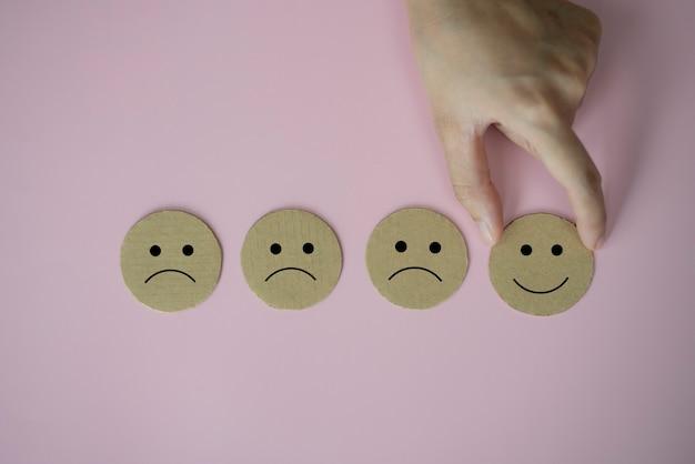 Main tenant le papier d'icône de visage de sourire de visage heureux coupé sur le fond rose
