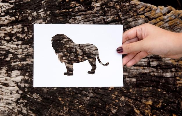 Main tenant le papier lion sculpture avec fond en bois
