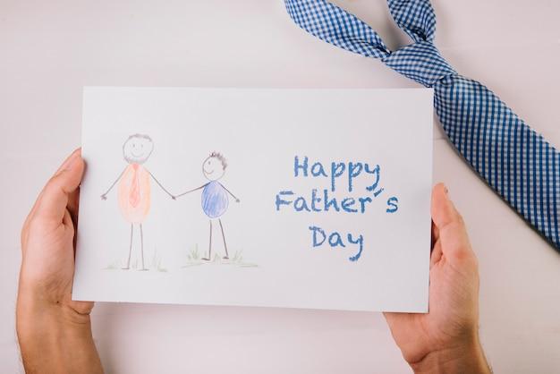 Main tenant un papier pour la fête des pères