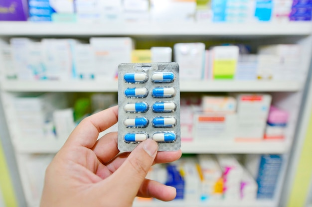Main tenant un paquet de capsules de médicaments à la pharmacie