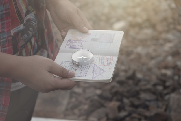 Main tenant un passeport de la boussole pour trouver des destinations de voyage. style vintage.