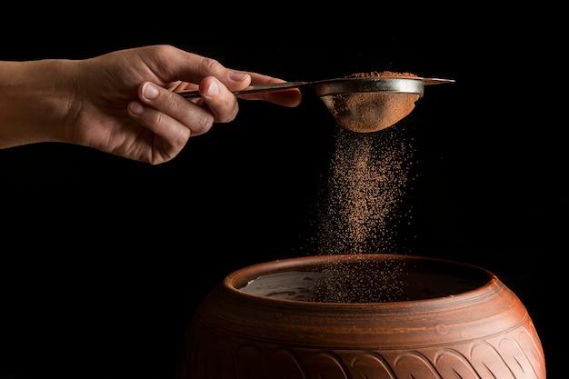 Main tenant une passoire avec de la poudre de cacao