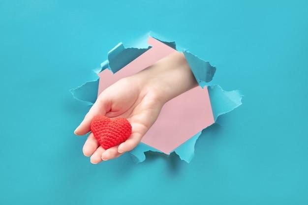 Main tenant un petit coeur à travers le trou dans le papier. concept d'amour et de soins