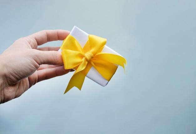 Main tenant une petite boîte cadeau avec ruban jaune